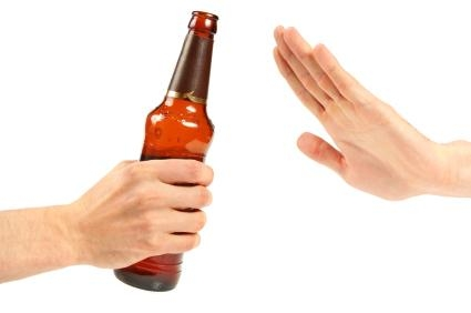 Hand gesturing to refuse a bottle of beer